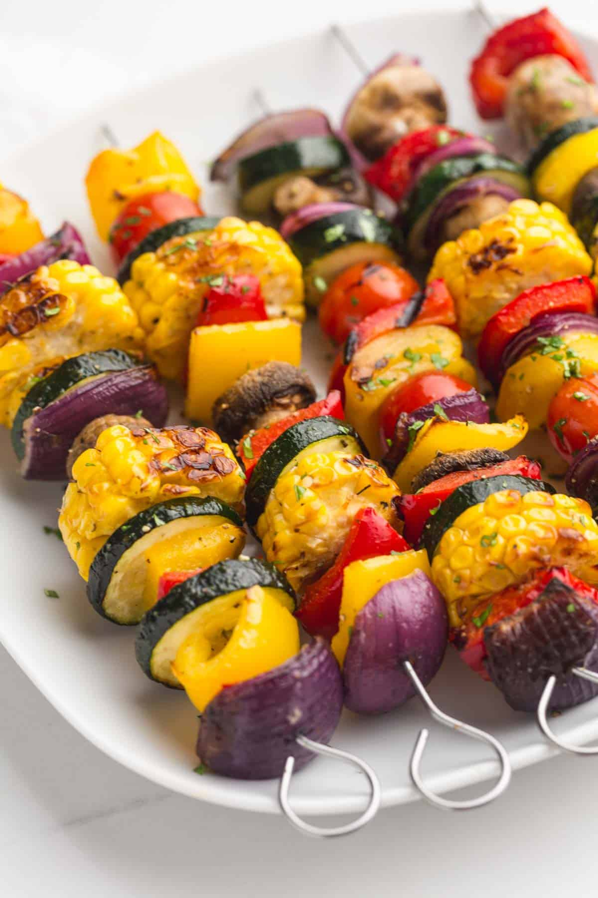 Close up of 5 vegetable skewers on a white plate