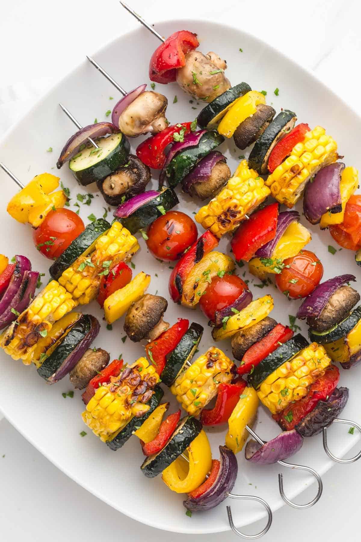 5 veggie kabobs on skewers, served on a white square plate