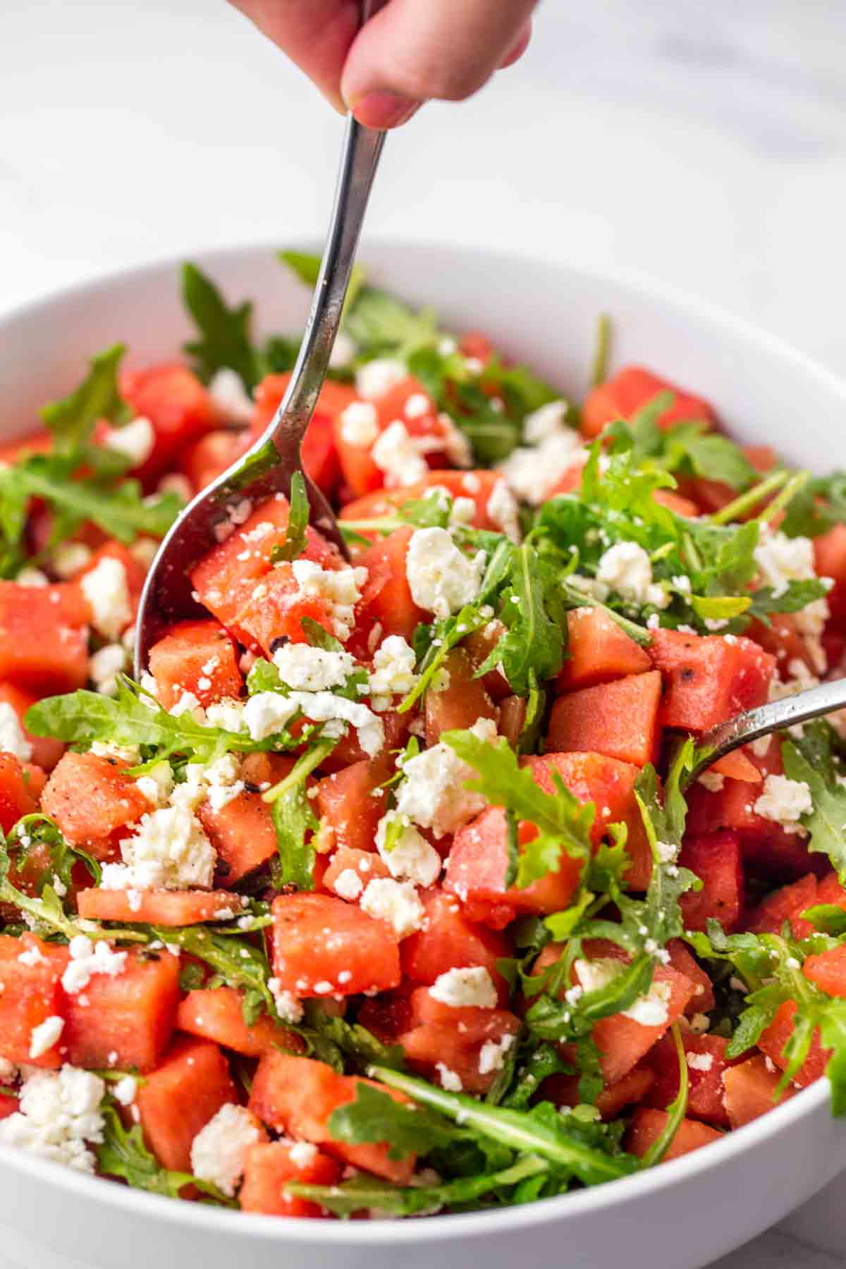 Two serving spoons used to serve watermelon salad from a large white salad bowl