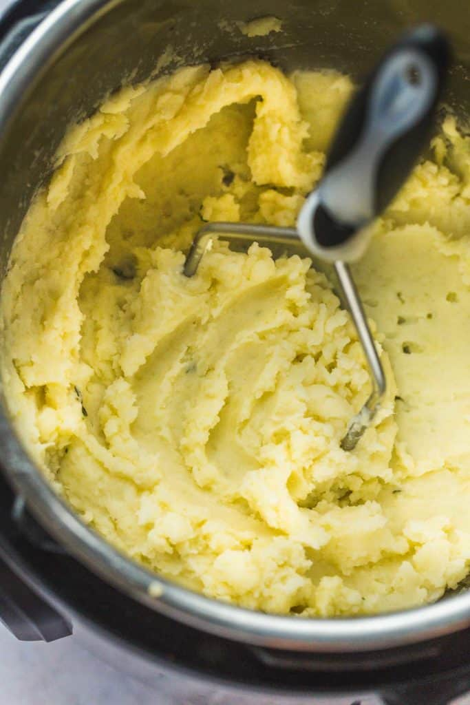 Super creamy whole30 mashed potatoes in the instant pot with a potato masher