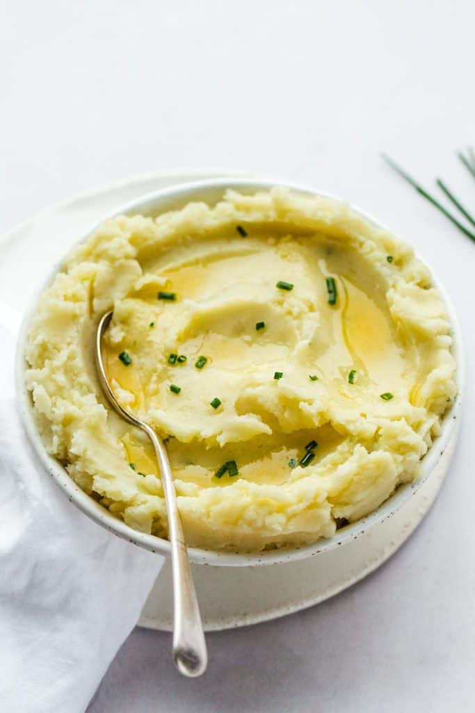 Super creamy mashed potatoes in a white bowl with a serving spoon