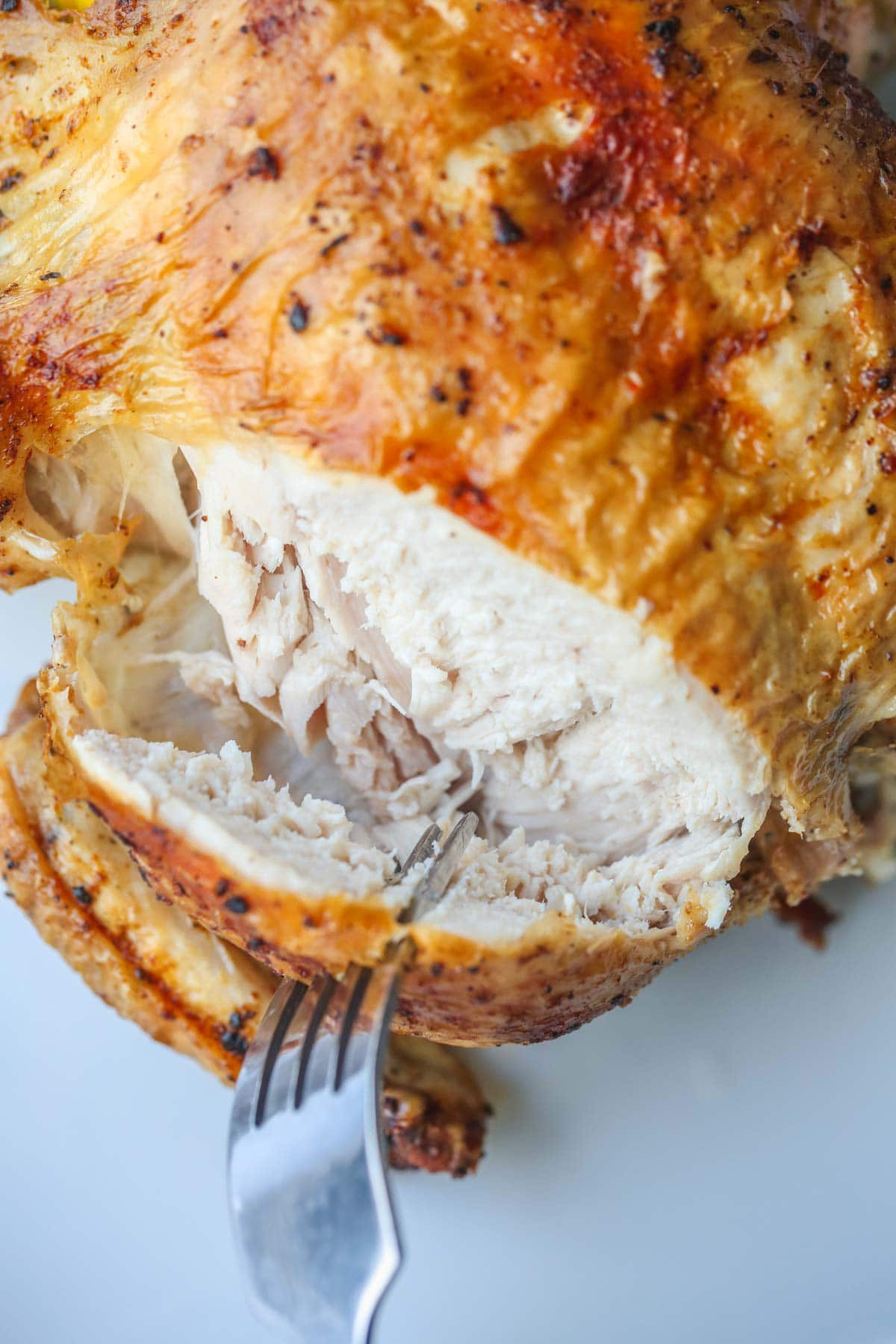 Cutting through the roast chicken breast, showing the doneness of the meat.