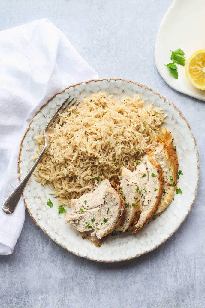 instant pot whole chicken rice on a plate with sliced chicken and a fork
