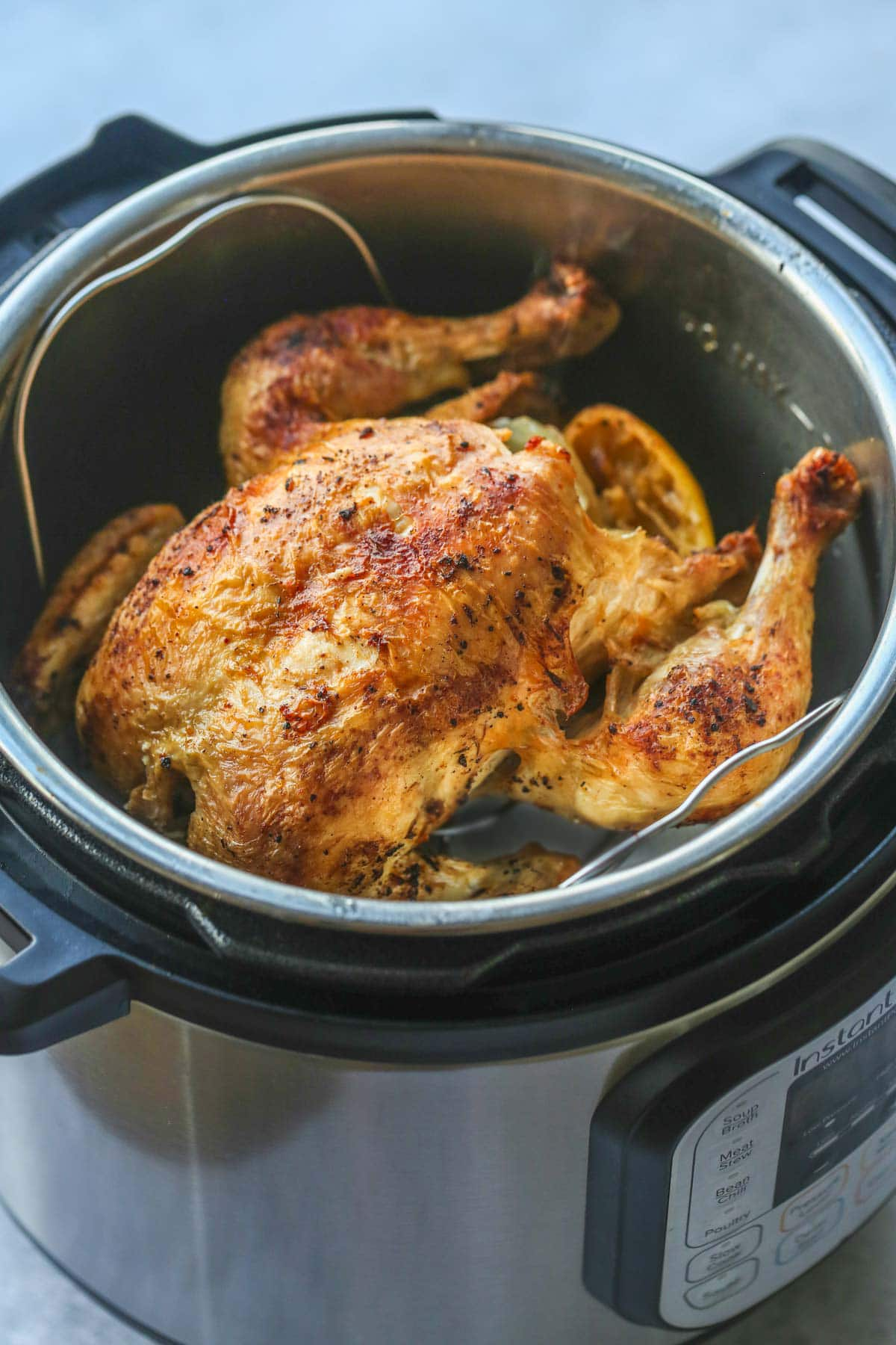 A whole cooked chicken inside the Instant Pot.