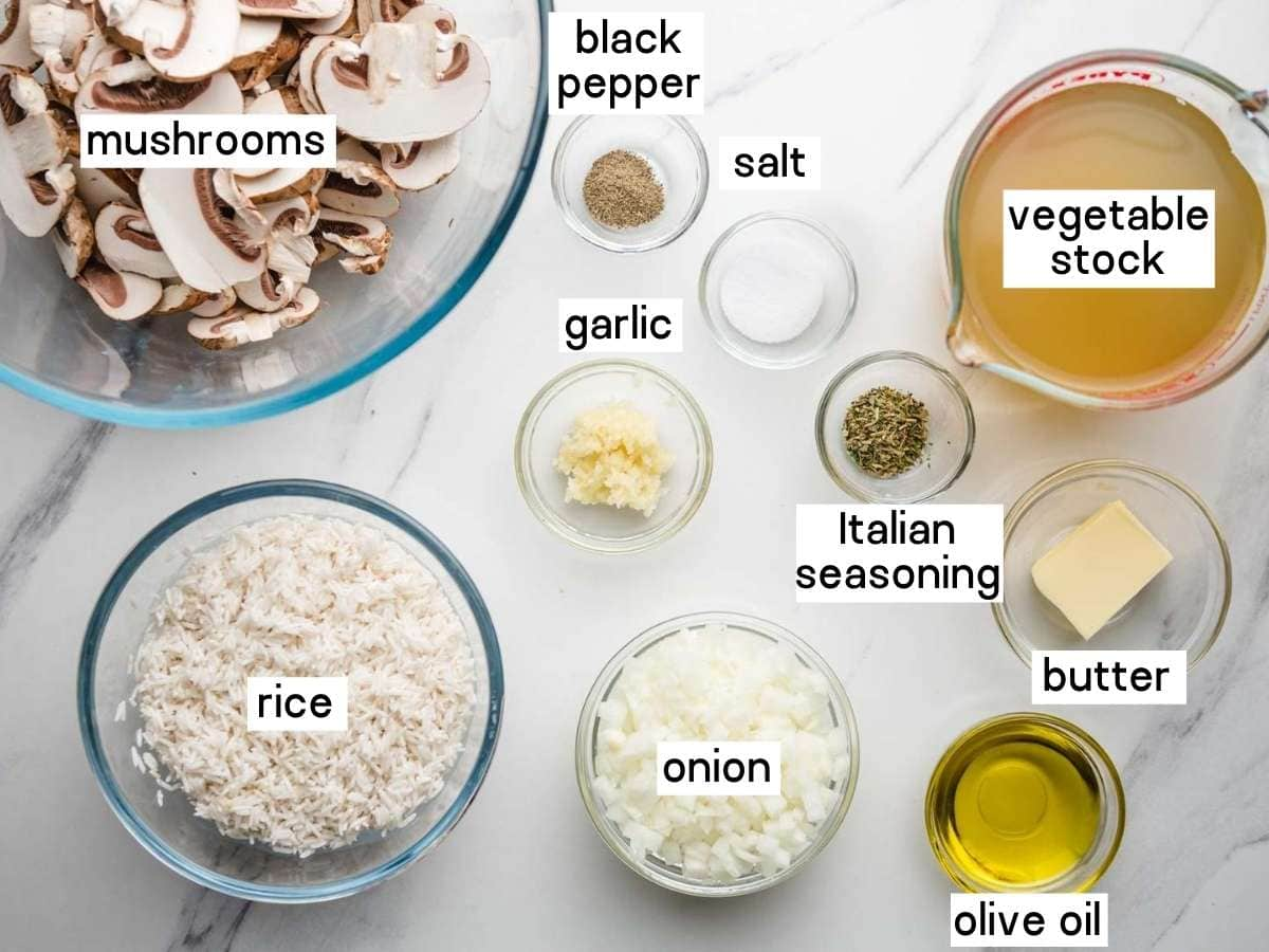 An overhead shot of ingredients needed to make mushroom rice including rice, sliced mushrooms, vegetable stock, butter, olive oil, diced onion, minced garlic, Italian seasoning, salt, and pepper.